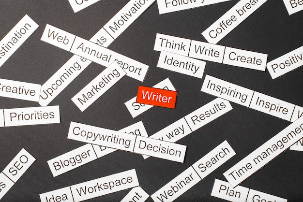 Corte o escritor de inscrição de papel em um vermelho, cercado por outras inscrições em um fundo escuro. palavra nuvem .