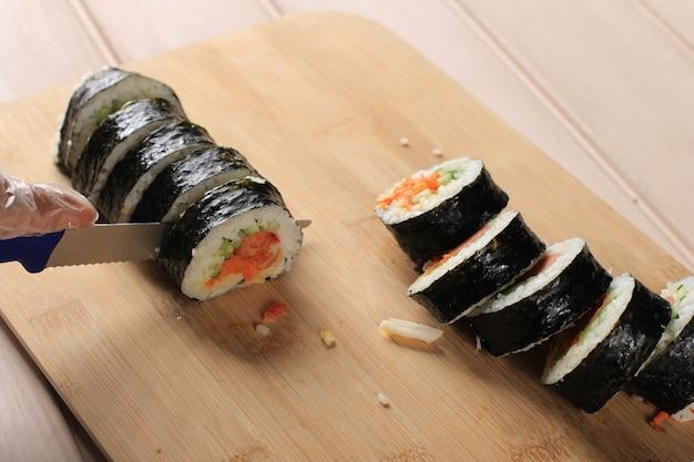 Corte o kimbap (prato de arroz com rolo coreano) com a faca azul. mulher mão usando luva de plástico, fazendo gimbap, cut kimbap, coreano roll gimbap (kimbob ou kimbap). passo a passo fazendo kimbop