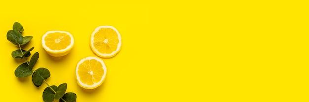Corte o limão, as rodelas de limão e um raminho de eucalipto em uma superfície amarela.