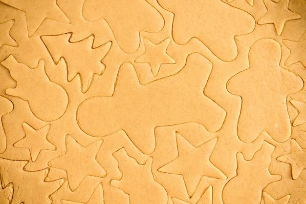 Corte o pão de gengibre da massa usando uma forma de pão de mel, vista de cima, massa crua com canela preparada para assar. o padrão na massa das figuras.