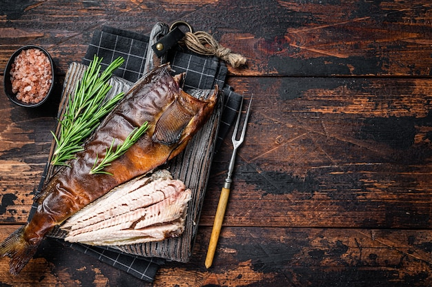 Corte o peixe defumado quente em uma placa de madeira com alecrim. fundo de madeira escuro. vista do topo. copie o espaço.