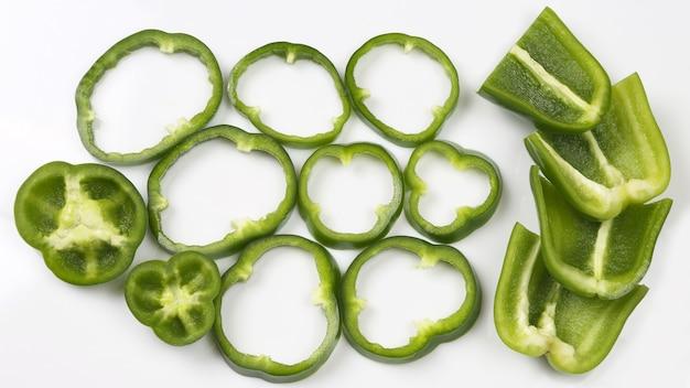 Corte o pimentão verde em pedaços no fundo branco. alimentos e vegetais frescos saudáveis