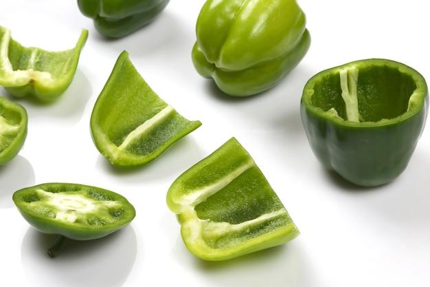Corte o pimentão verde em pedaços no fundo branco. alimentos vitamínicos úteis