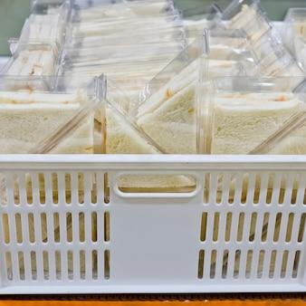 Corte o prato de triângulos de sanduíche em caixa de plástico pronta para vender