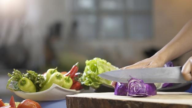 Corte o repolho roxo com faca de cozinha na placa de madeira, close-up
