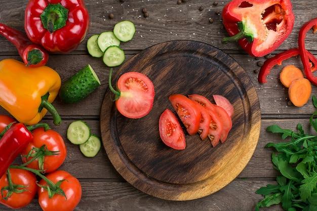 Corte o tomate em uma placa de madeira e os vegetais em uma mesa. copie o espaço. vista do topo