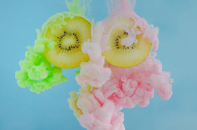 Corte os kiwis com foco parcial de dissolver a cor de pôster rosa e verde na água.