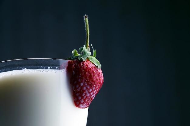 Corte os morangos em um copo com leite