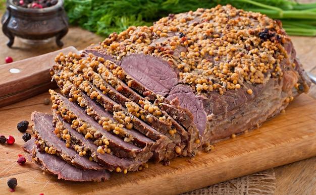 Corte pedaços de carne assada na mesa