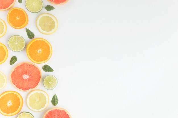 Corte pedaços de frutas cítricas e folhas