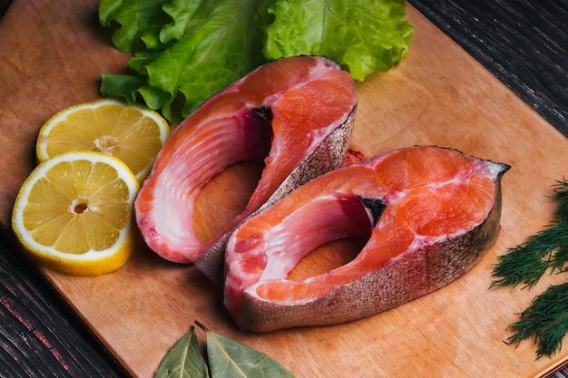 Corte pedaços de peixe vermelho a bordo. filé de truta fresca