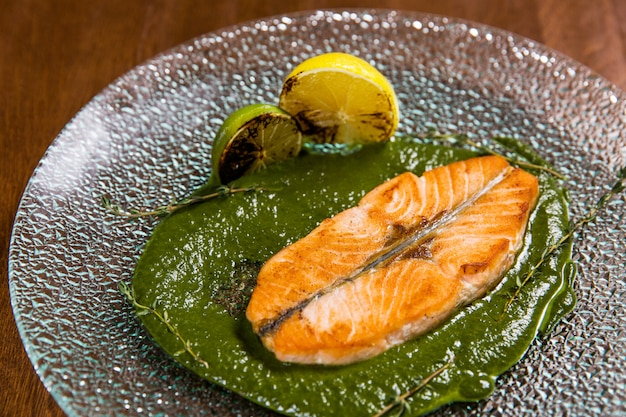 Corte peixe com limão e molho no prato de vidro na mesa de madeira no restaurante de luxo