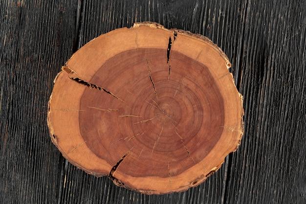 Corte redondo de árvore na mesa de madeira escura