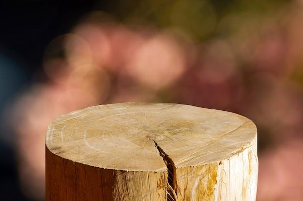 Corte redondo de serra de madeira em forma de cilindro para exposição de produto com fundo abstrato bokeh rosa