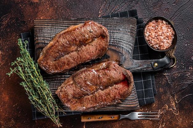 Corte shoulder top blade assado na churrasqueira ou bife de lâmina de ostra australiana wagyu. fundo escuro. vista do topo.