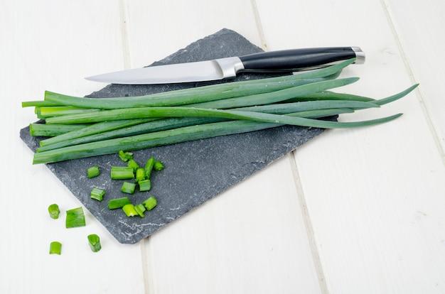 Corte talos de cebolinha, um ingrediente na culinária