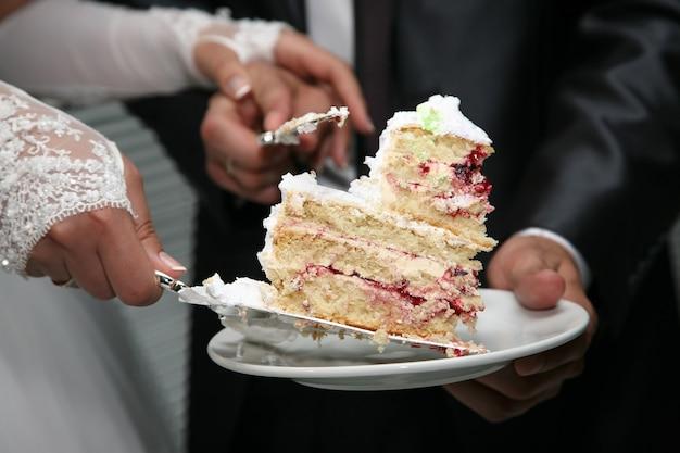 Corte um pedaço de bolo de casamento nas mãos da noiva e do noivo