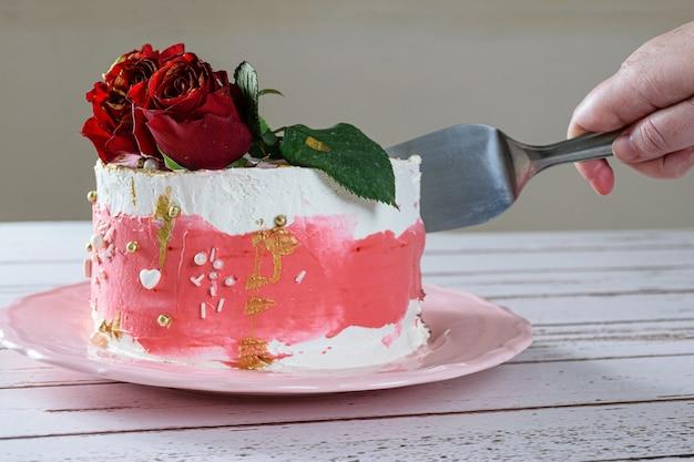Corte uma fatia de bolo de chocolate coberto com creme de manteiga de merengue suíço (vista lateral).