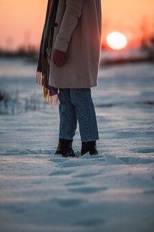 Corte uma mulher irreconhecível com roupas quentes e botas na neve branca fresca na zona rural de inverno ao pôr do sol