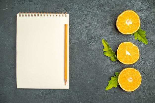 Corte vertical em linha superior, corte laranjas, caderno e lápis em superfície escura