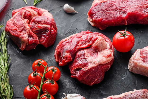 Cortes de bife de carne de rolo de olho de mandril cru, com ervas, tempero na mesa preta, vista lateral.