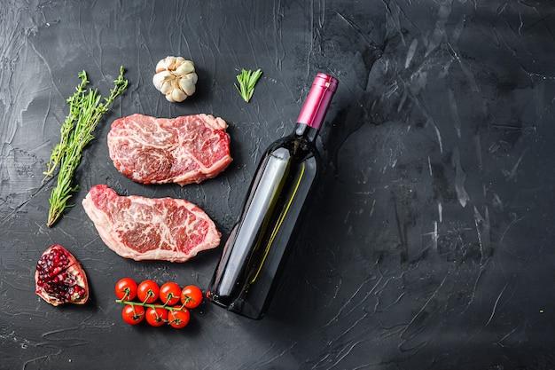 Cortes de bife orgânicos, com garrafa de vinho tinto e copos, ervas e temperos