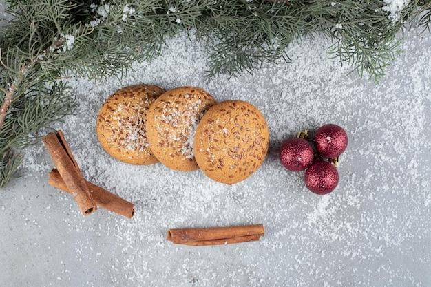 Cortes de canela perfumados, biscoitos, bolas decorativas e um galho na mesa de mármore.