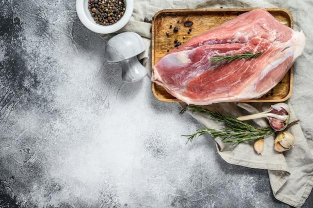 Cortes de carne de porco fresca. carne crua com especiarias. parte traseira do ombro. fundo cinza. vista do topo