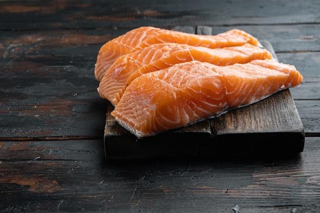 Cortes de filé de salmão cru fresco, na velha mesa de madeira