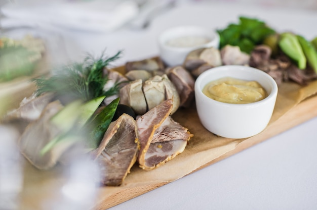 Cortes frios em uma placa de desbastamento de madeira. banquete no restaurante