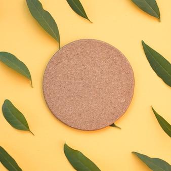 Cortiça circular em branco rodeada de folhas verdes em fundo amarelo