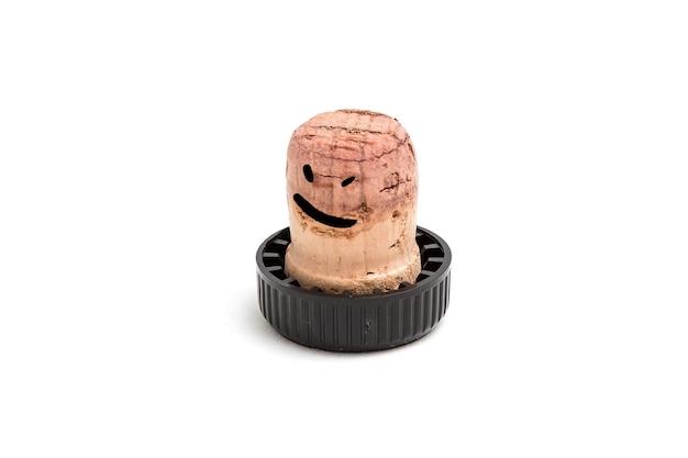 Cortiça para vinho com um chapéu de plástico preto é desenhada com um sorriso e olhos bêbados