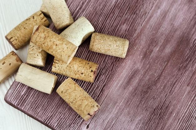 Cortiça usadas da garrafa com vinho tinto na superfície de madeira.