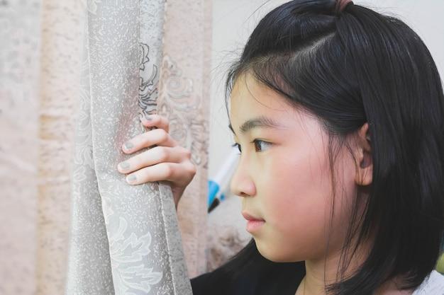 Cortina aberta da menina que olha fora com espírito ausente, conceito esperançoso