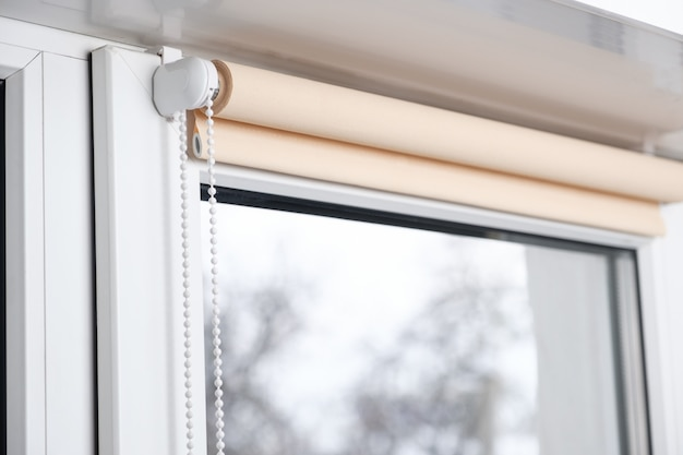 Cortina de rolo bege do apagão na janela plástica branca. persianas na janela de plástico.