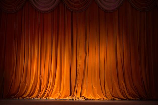 Cortina marrom-avermelhada no palco com piso de madeira e textura de fundo nos bastidores do teatro