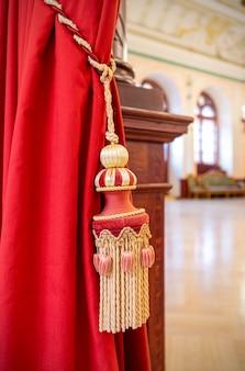 Cortina vermelha com escova de cortina ou borla de corda