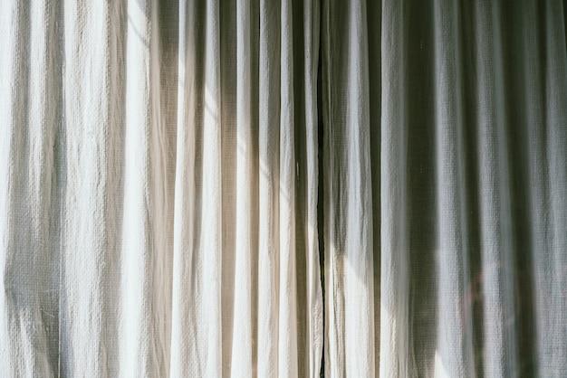 Cortinas antigas de lona cinza com sombra e luz do sol na decoração da casa em estilo minimalista