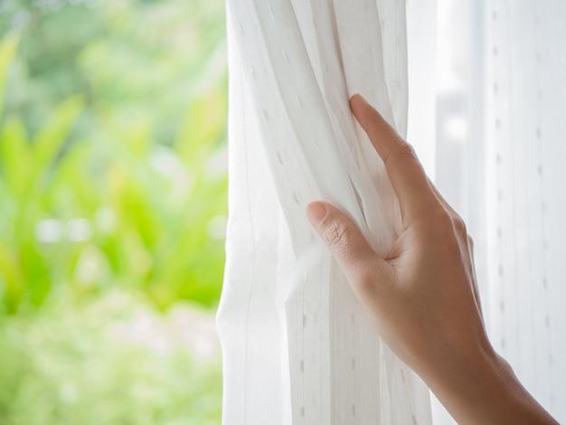 Cortinas de abertura da mão da mulher no quarto com luz natural e fundo do jardim.