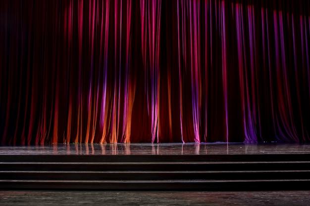 Cortinas vermelhas e palco de madeira.