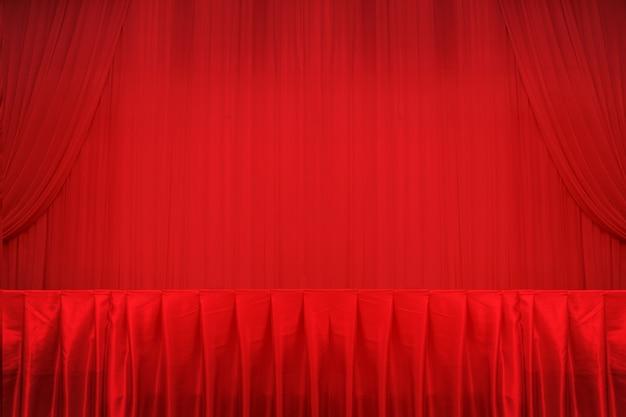 Cortinas vermelhas e palco e mesa.