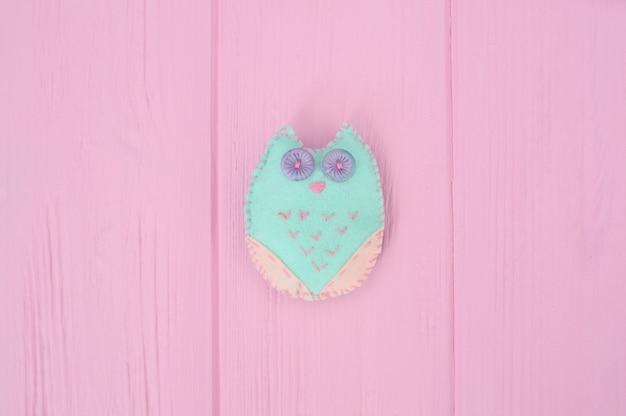Coruja de brinquedo macio feita a mão de artesanato de feltro em uma madeira rosa