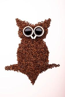 Coruja feita de grãos de café torrados e duas xícaras em fundo branco.