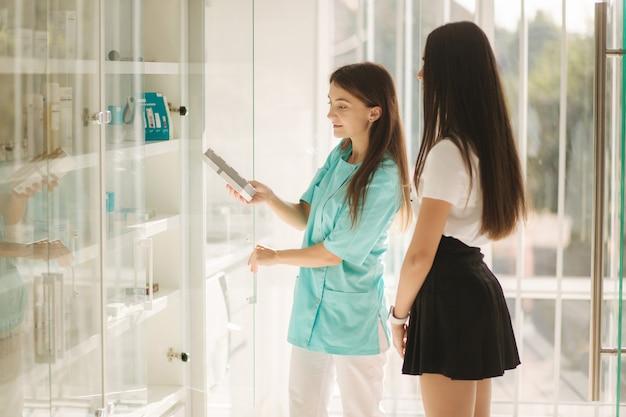 Cosmética feminina mostra ao cliente um produto de cosmetologia. o médico recomenda diferentes soro e rosto