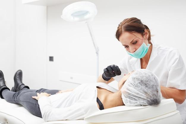 Cosmetician aplica maquiagem permanente nos lábios