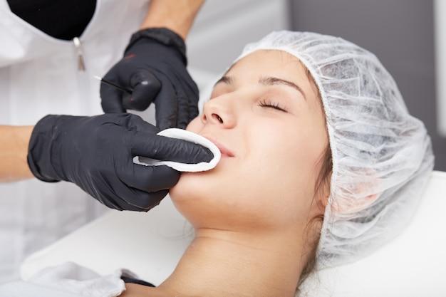 Cosmetician aplicar maquiagem permanente nos lábios