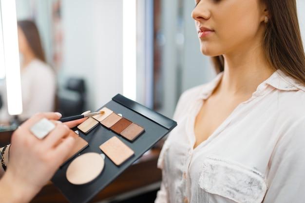 Cosmeticista coloca sombras no rosto de uma mulher em uma loja de cosméticos. salão de beleza luxuoso, cliente e esteticista no mercado da moda