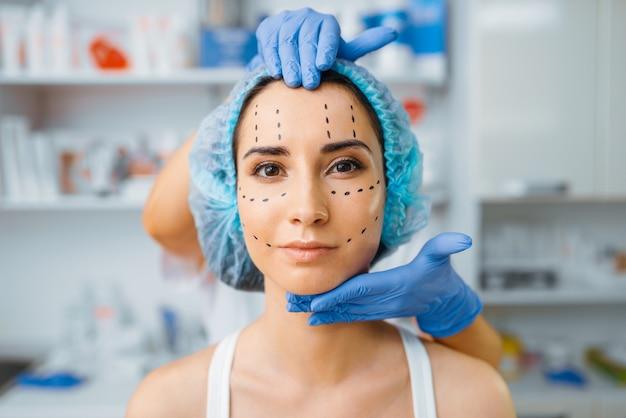 Cosmeticista e paciente do sexo feminino com marcadores no rosto. procedimento de rejuvenescimento em salão de esteticista. cirurgia estética contra rugas, preparação para o botox