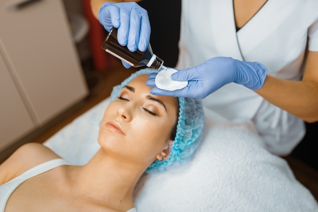Cosmeticista e paciente do sexo feminino, limpeza de pele facial. procedimento de rejuvenescimento em salão de esteticista.