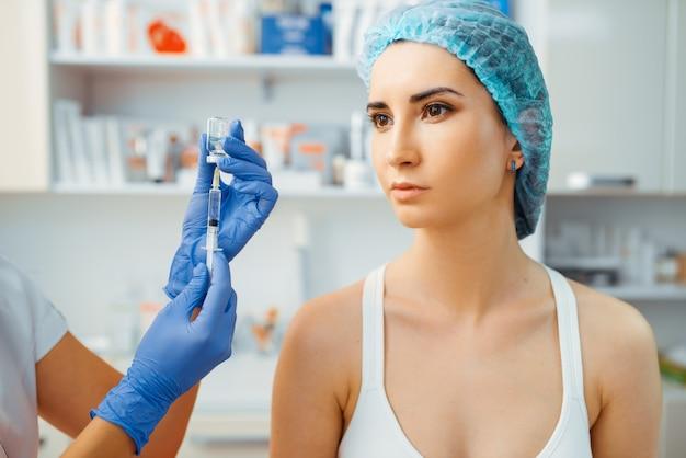 Cosmeticista faz terapia de botox para paciente do sexo feminino na mesa de tratamento. procedimento de rejuvenescimento em salão de esteticista.